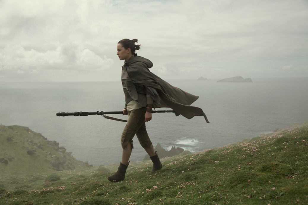 Rey walking with staff on island
